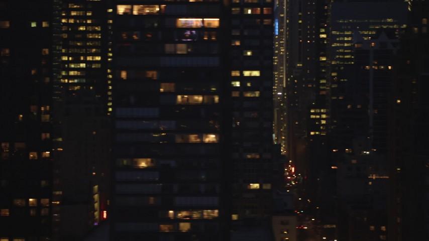 5K stock footage aerial video of busy streets between blocks of skyscrapers in Midtown Manhattan, New York City, winter, night Aerial Stock Footage | AX65_0274