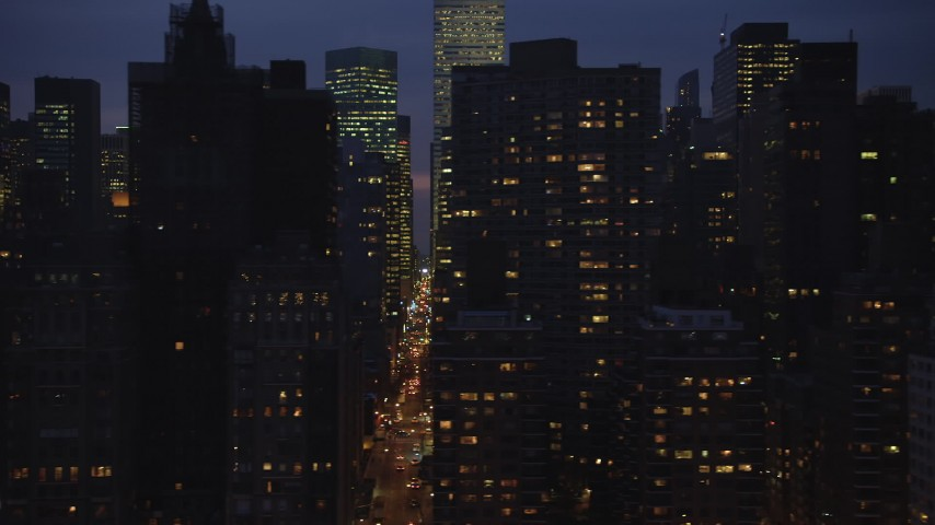 5K stock footage aerial video flyby busy streets between rows of skyscrapers in Midtown Manhattan, New York City, winter, night Aerial Stock Footage | AX65_0275