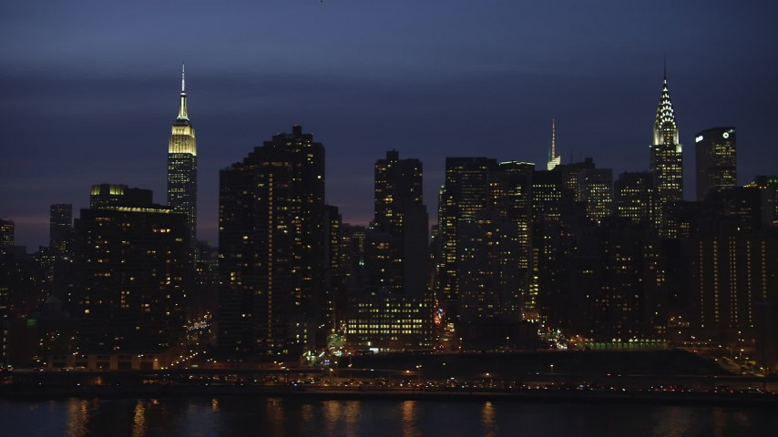 Flyby riverfront condos between Empire State Building and Chrysler Building in Midtown Manhattan, New York City, winter, night Aerial Stock Footage | AX65_0278