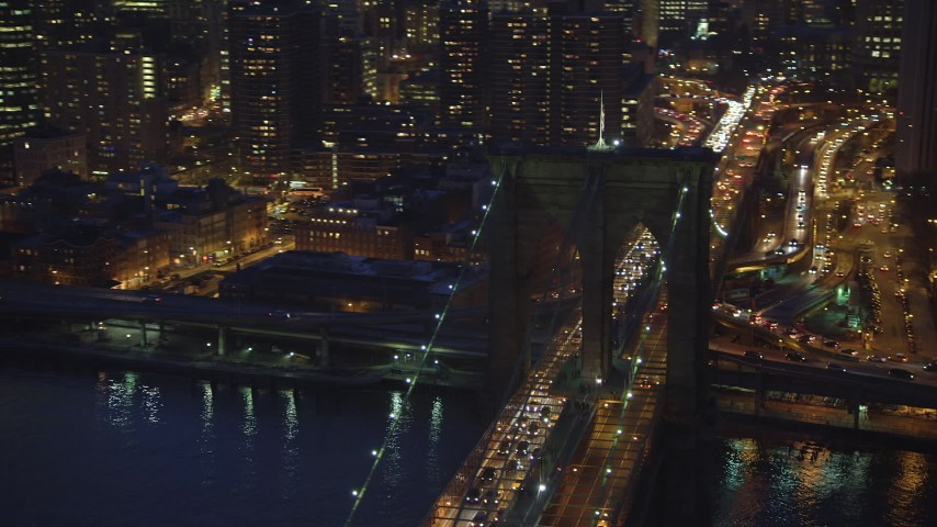 5K stock footage aerial video track an arch in the Brooklyn Bridge with heavy traffic, Lower Manhattan, New York City, winter, night Aerial Stock Footage AX65_0282 | Axiom Images