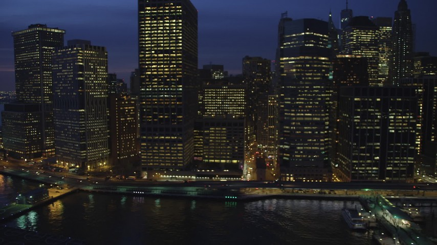 Riverfront skyscrapers and the Staten Island Ferry Terminal in Lower Manhattan, New York City, winter, night Aerial Stock Footage | AX65_0284