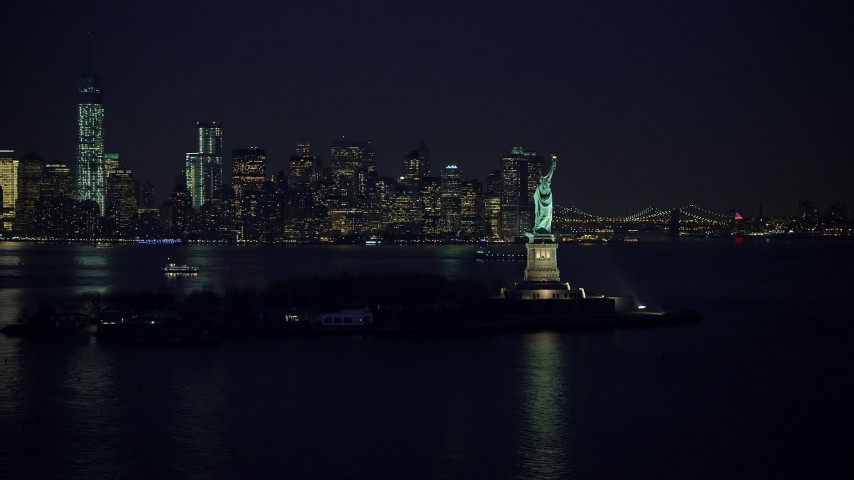 Statue of Liberty and the skyline of Lower Manhattan, New York City, winter, night Aerial Stock Footage | AX65_0285