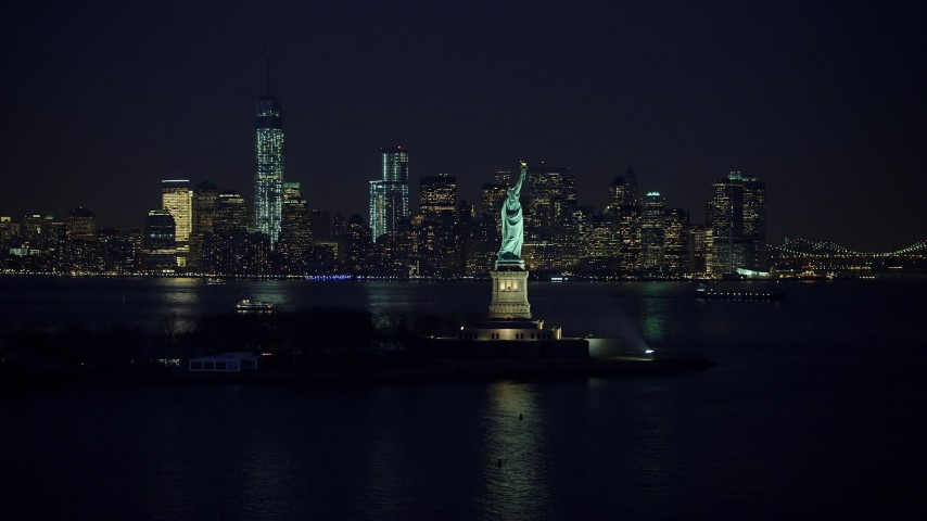 Statue of Liberty, and the skyline of Lower Manhattan in the background, New York City, winter, night Aerial Stock Footage | AX65_0286