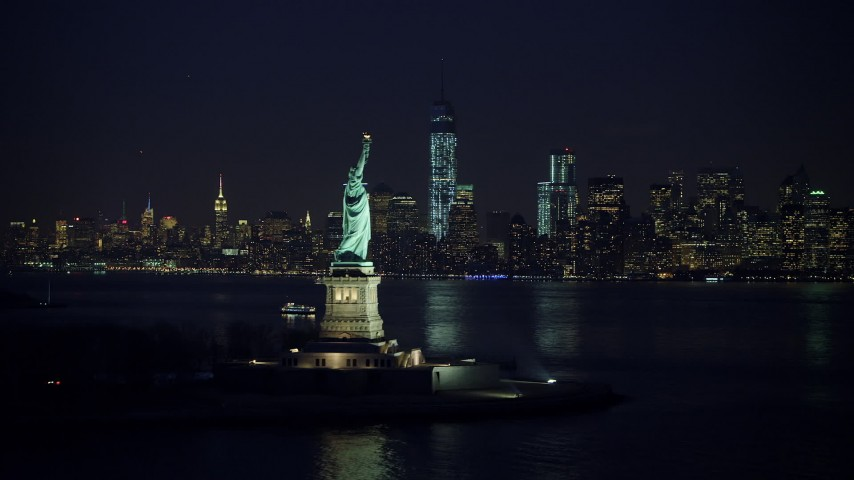 5K stock footage aerial video of Statue of Liberty, and the skyline of Lower Manhattan and Freedom Tower in the background, New York City, winter, night Aerial Stock Footage AX65_0287 | Axiom Images