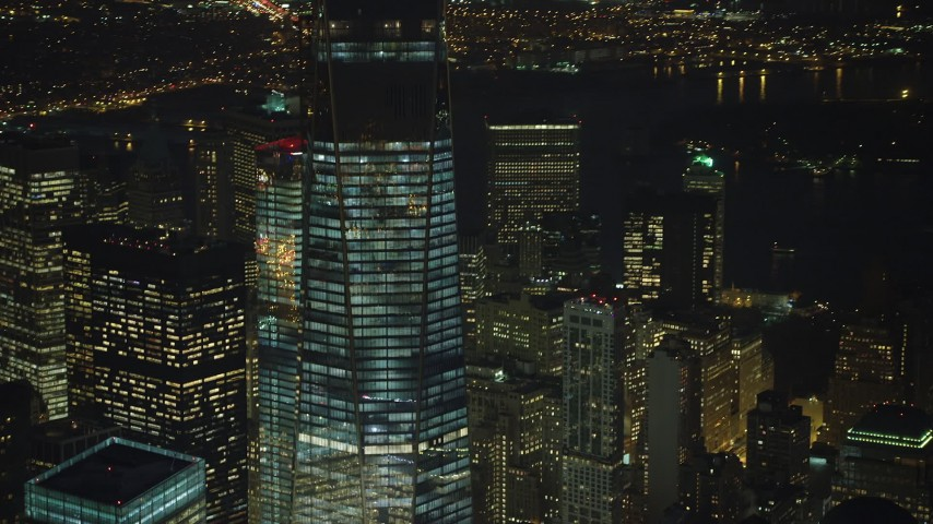 Orbit and tilt to the top of One World Trade Center skyscraper in Lower Manhattan, New York City, winter, night Aerial Stock Footage | AX65_0298