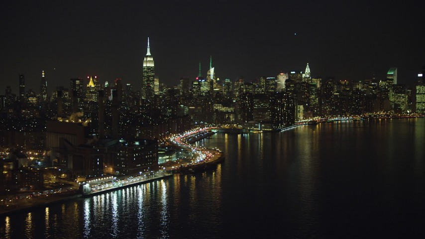 5K stock footage aerial video flyby a riverfront power plant, Empire State Building, and the Midtown Manhattan skyline, New York City, winter, night Aerial Stock Footage | AX65_0304