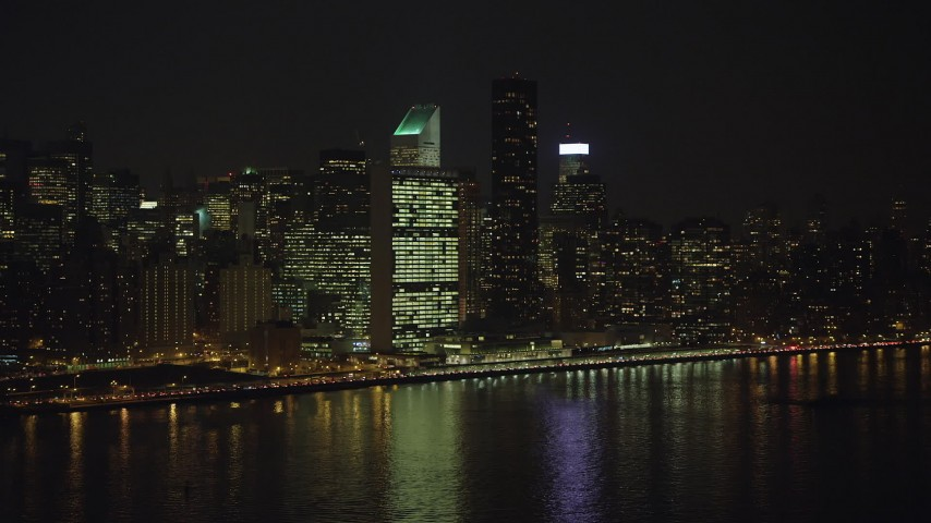 Approach the United Nations building in Midtown Manhattan, New York City, winter, night Aerial Stock Footage | AX65_0306
