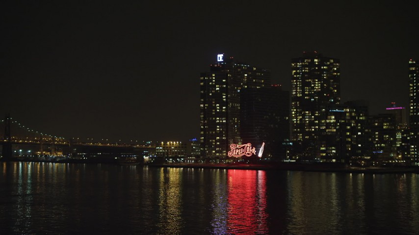 5K stock footage aerial video fly low over the East River to approach the Pepsi Sign and riverfront apartment buildings in Queens, NYC, winter, night Aerial Stock Footage | AX65_0309