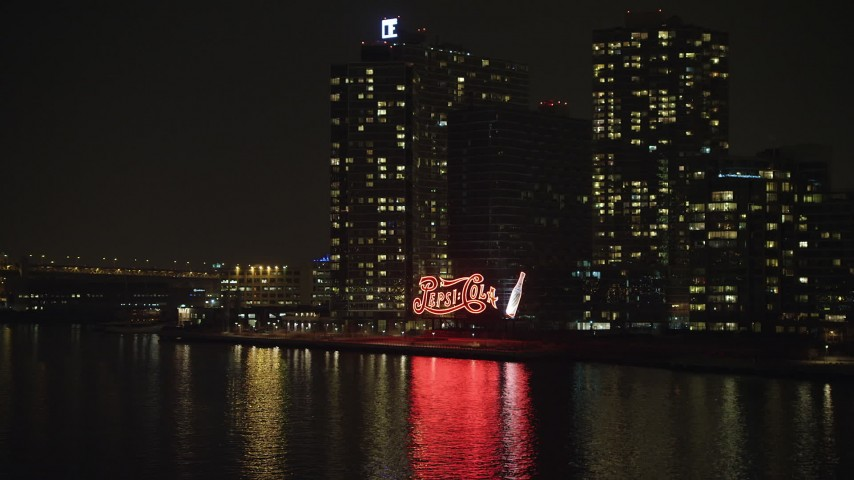 Fly low to approach the Pepsi Sign and riverfront apartment buildings in Queens, New York City, winter, night Aerial Stock Footage | AX65_0310