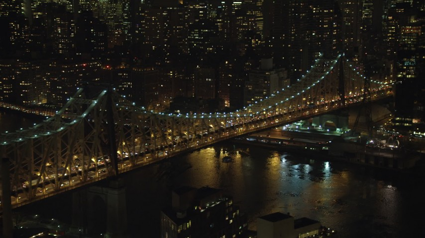 5K stock footage aerial video tilt from the Queensboro Bridge to reveal Midtown Manhattan skyscrapers, New York City, winter, night Aerial Stock Footage | AX65_0312