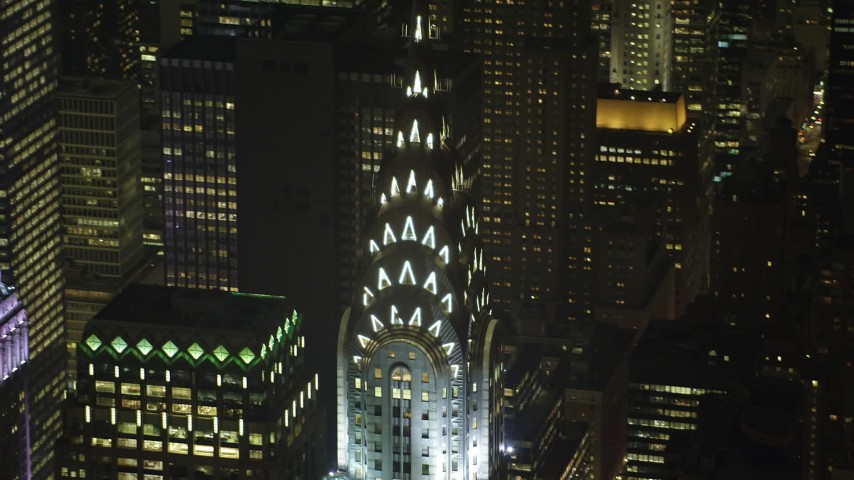 Orbit and tilt down the side of the Chrysler Building in Midtown Manhattan, New York City, winter, night Aerial Stock Footage | AX65_0316