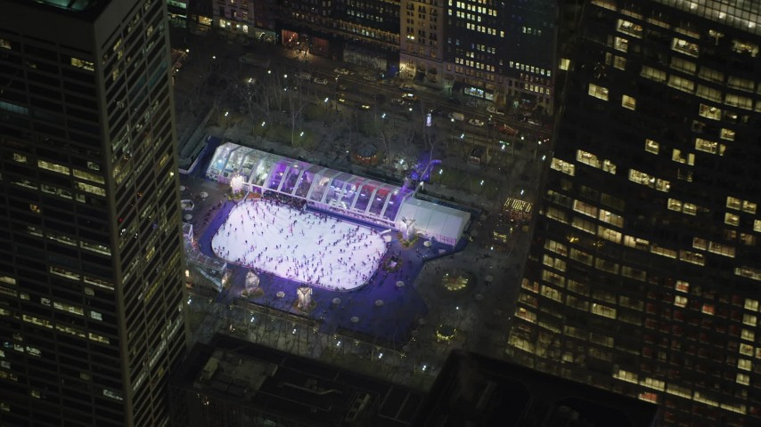 5K stock footage aerial video orbit the ice skating rink at Bryant Park and a skyscraper in Midtown Manhattan, New York City, winter, night Aerial Stock Footage | AX65_0328