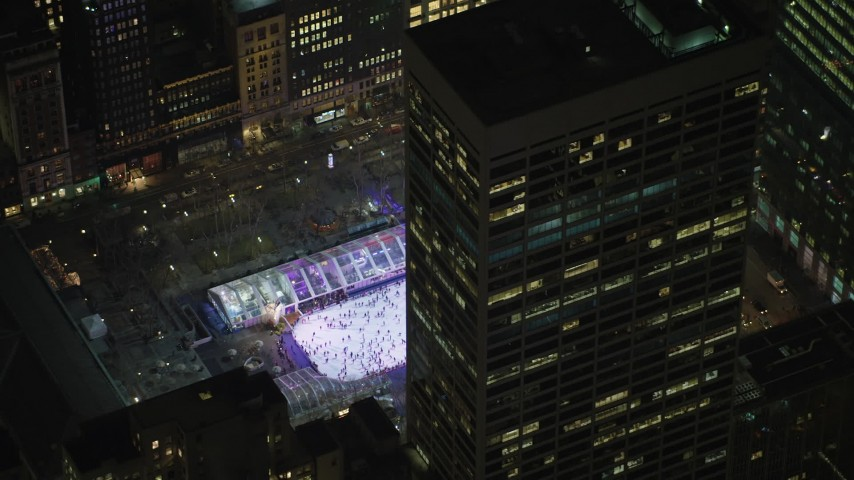 5K stock footage aerial video orbit a skyscraper to reveal the ice skating rink at Bryant Park in Midtown Manhattan, New York City, winter, night Aerial Stock Footage | AX65_0329