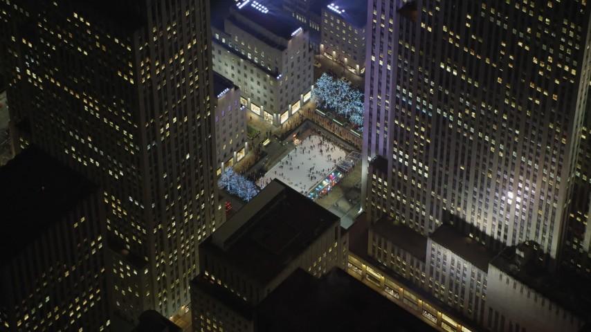 5K stock footage aerial video orbit Rockefeller Center ice skating rink, Midtown Manhattan, New York City, winter, night Aerial Stock Footage | AX65_0333