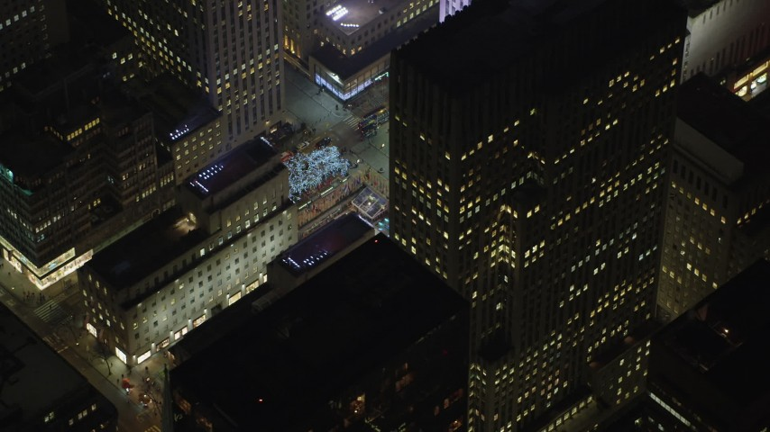 5K stock footage aerial video orbit Rockefeller Center skyscraper to reveal the ice skating rink, Midtown Manhattan, New York City, winter, night Aerial Stock Footage | AX65_0335