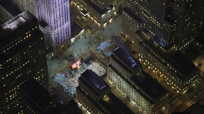 5K stock footage aerial video tilt to a bird's eye view of the Rockefeller Center ice skating rink, Midtown Manhattan, New York City, winter, night Aerial Stock Footage | AX65_0337