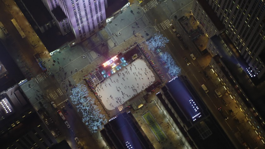A bird's eye view of the Rockefeller Center ice skating rink, Midtown Manhattan, New York City, winter, night Aerial Stock Footage | AX65_0338