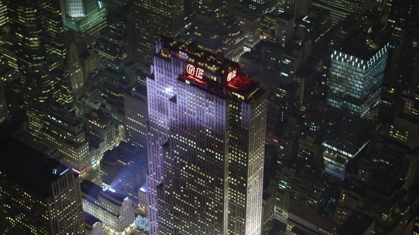 5K stock footage aerial video of flying away from Rockefeller Center in Midtown Manhattan, New York City, winter, night Aerial Stock Footage | AX65_0339