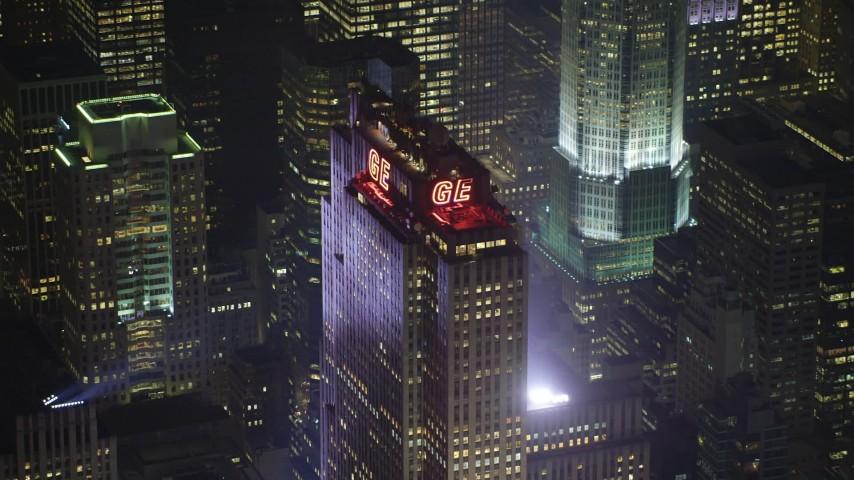 Tracking top of Rockefeller Center skyscraper in Midtown Manhattan, New York City, winter, night Aerial Stock Footage | AX65_0340