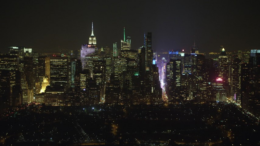 Midtown Manhattan and bright lights of Times Square seen from Central Park, New York City, winter, night Aerial Stock Footage | AX65_0345