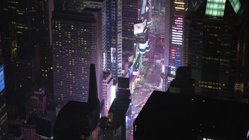 5K stock footage aerial video approach bright lights and tourists at Times Square in Midtown Manhattan, New York City, winter, night Aerial Stock Footage | AX65_0352