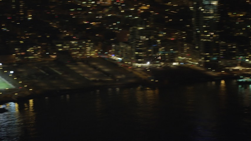 5K stock footage aerial video track a helicopter flying by the Midtown Manhattan riverfront, New York City, winter, night Aerial Stock Footage | AX65_0366