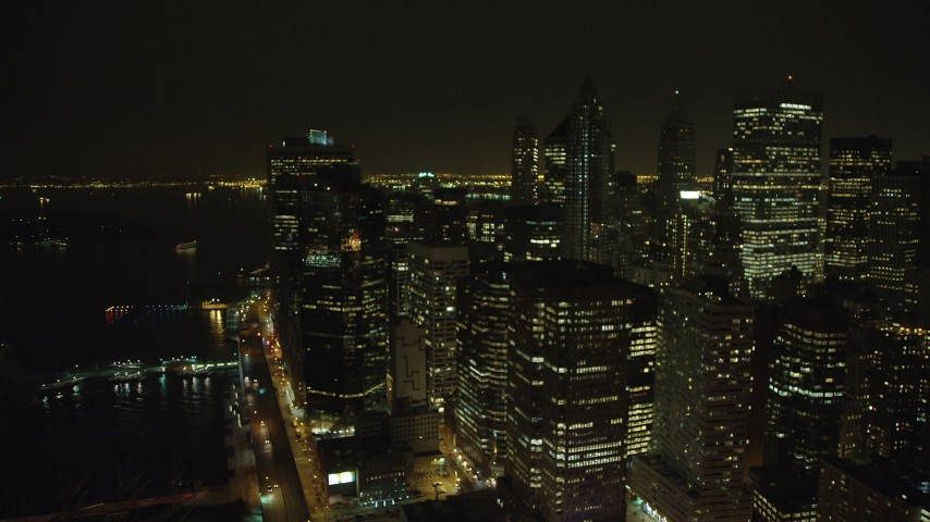 Flyby skyscrapers beside the East River in Lower Manhattan, New York City, winter, night Aerial Stock Footage | AX65_0367