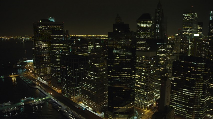 5K stock footage aerial video of passing skyscrapers beside the East River in Lower Manhattan, New York City, winter, night Aerial Stock Footage | AX65_0368