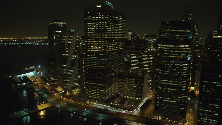 5K stock footage aerial video of tall riverfront skyscrapers beside the East River in Lower Manhattan, New York City, winter, night Aerial Stock Footage | AX65_0369