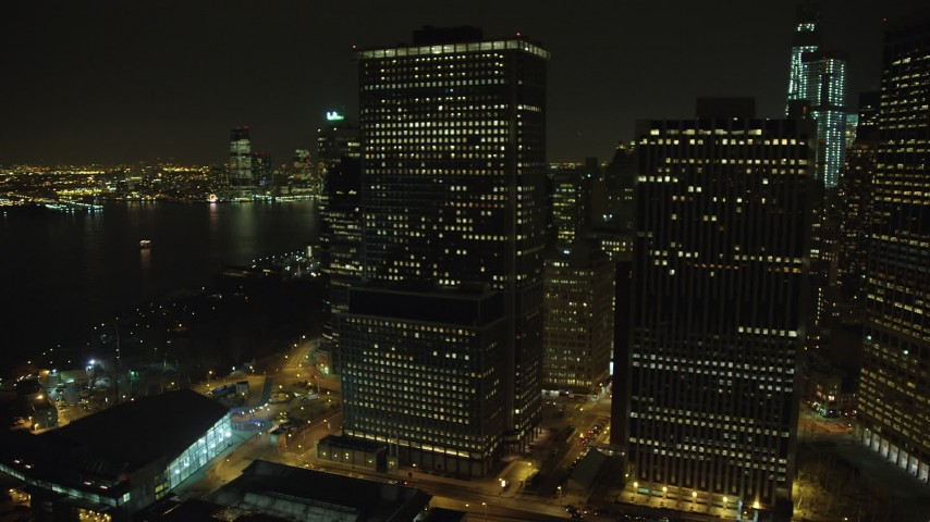 5K stock footage aerial video of tall riverfront skyscrapers and Battery Park in Lower Manhattan, New York City, winter, night Aerial Stock Footage | AX65_0370