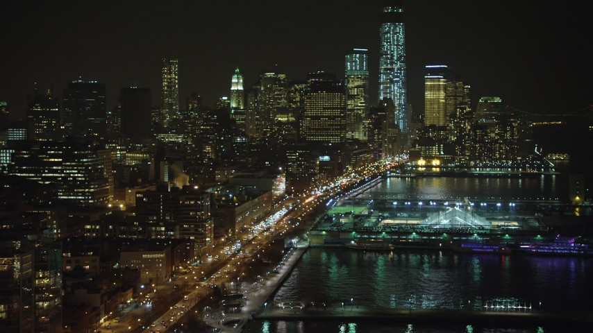 Fly over Pier 40 and West Street to approach skyscrapers in Lower Manhattan, New York City, winter, night Aerial Stock Footage | AX65_0374