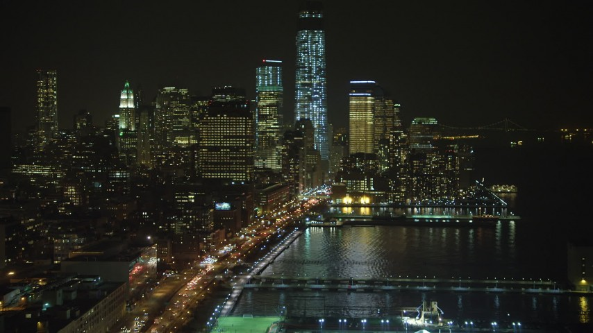 5K stock footage aerial video follow West Street to approach One World Trade Center in Lower Manhattan, New York City, winter, night Aerial Stock Footage | AX65_0375