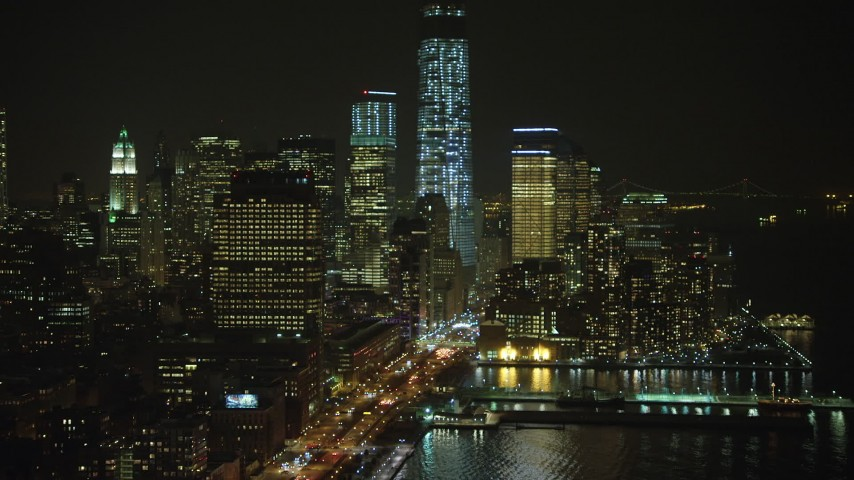 Approach Freedom Tower and World Trade Center skyscrapers in Lower Manhattan, New York City, winter, night Aerial Stock Footage | AX65_0376
