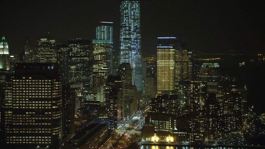 5K stock footage aerial video approach base of Freedom Tower and World Trade Center skyscrapers, tilt toward West Street in Lower Manhattan, NYC, winter, night Aerial Stock Footage | AX65_0377
