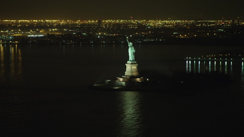 5K stock footage aerial video of tracking the Statue of Liberty and Liberty Island in New York, winter, night Aerial Stock Footage | AX65_0383
