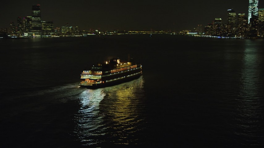 Track Staten Island Ferry sailing New York Harbor, reveal Lower Manhattan skyline, New York City, winter, night Aerial Stock Footage | AX65_0386