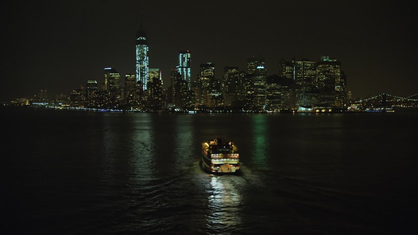 5K stock footage aerial video flyby Staten Island Ferry sailing toward Lower Manhattan skyline, New York City, winter, night Aerial Stock Footage | AX65_0387