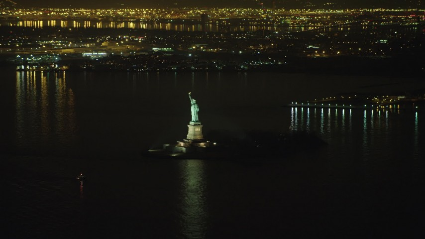 5K stock footage aerial video of flying by the Statue of Liberty monument on Liberty Island in New York, winter, night Aerial Stock Footage | AX65_0389