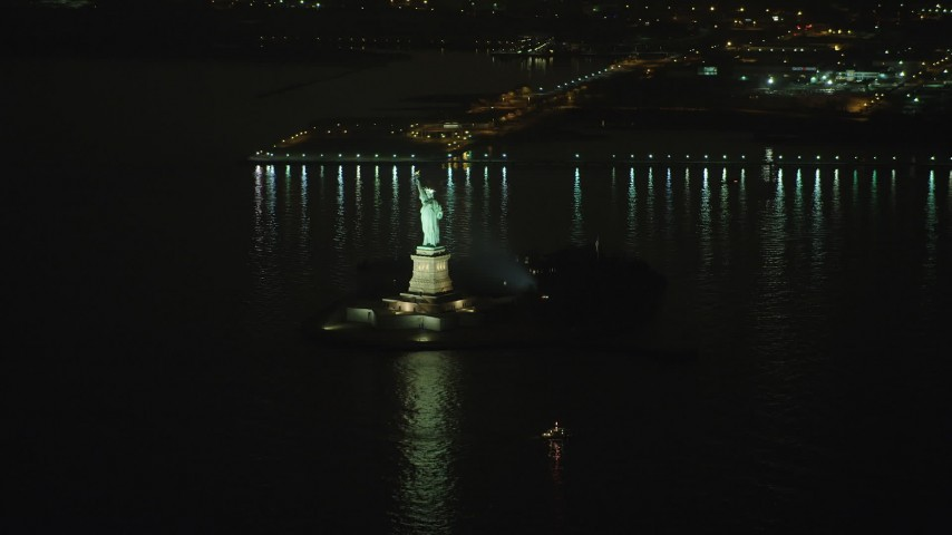 Approach Statue of Liberty as a helicopter flies by in New York, winter, night Aerial Stock Footage | AX65_0391