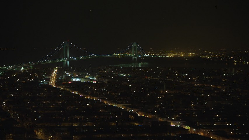 A view of the Verrazano-Narrows Bridge from Brooklyn neighborhoods in New York City, winter, night Aerial Stock Footage | AX65_0397