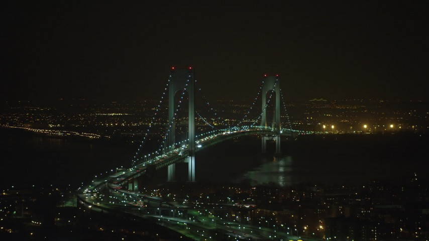 Passing by the Verrazano-Narrows Bridge in New York City, winter, night Aerial Stock Footage | AX65_0399