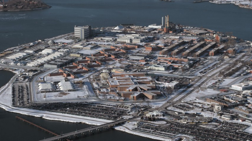 5K stock footage aerial video of flying by prison buildings Rikers Island Prison in snow, New York Aerial Stock Footage | AX66_0050