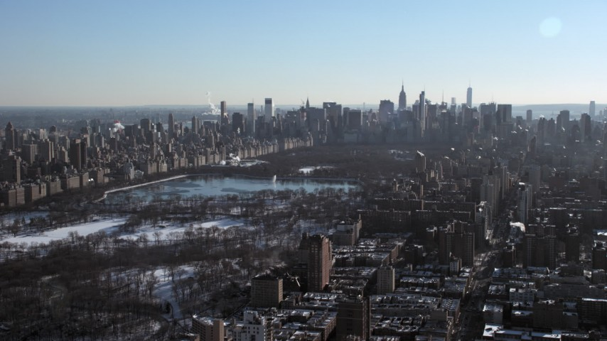 5K stock footage aerial video of a wide view of Central Park in snow and Midtown Manhattan skyscrapers, New York City Aerial Stock Footage | AX66_0100
