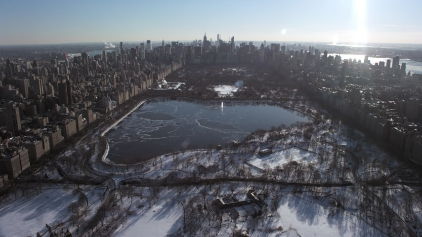 5K aerial video of over Central Park with snow and approach the icy reservoir, New York City Aerial Stock Footage | AX66_0103