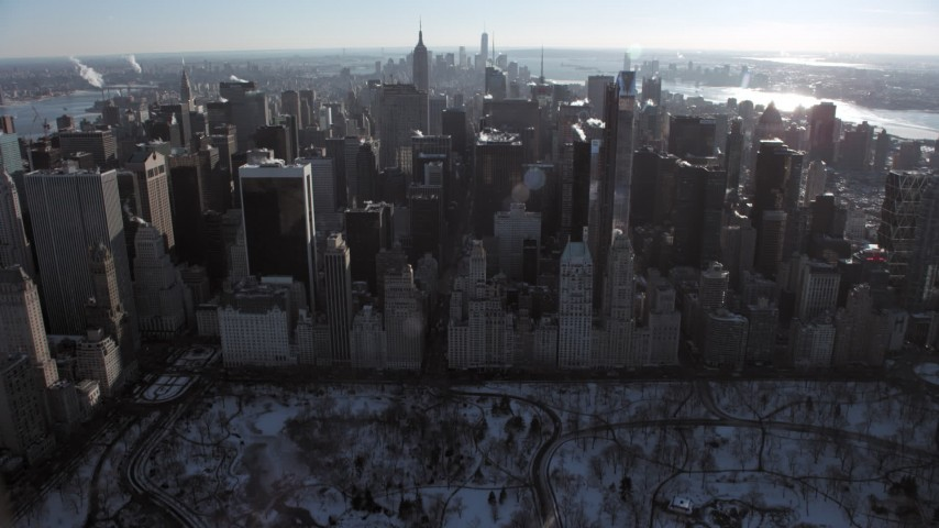 5K stock footage aerial video tilt from Central Park to reveal Midtown Manhattan in winter, New York City Aerial Stock Footage | AX66_0107