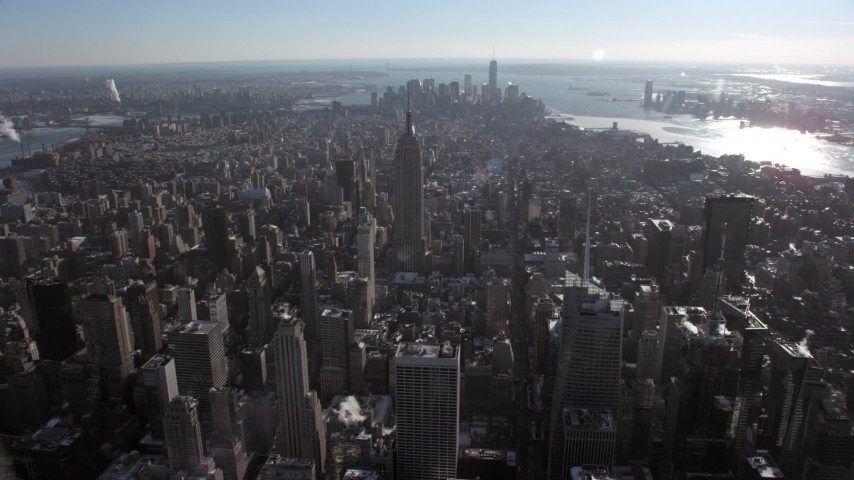 5K stock footage aerial video fly over Midtown's skyscrapers, approach the famous Empire State Building in snow, New York City Aerial Stock Footage | AX66_0111
