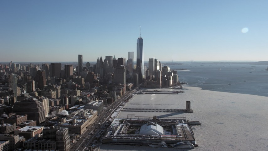 5K stock footage aerial video of the World Trade Center skyline beside Hudson River with ice, New York City Aerial Stock Footage   AX66_0117