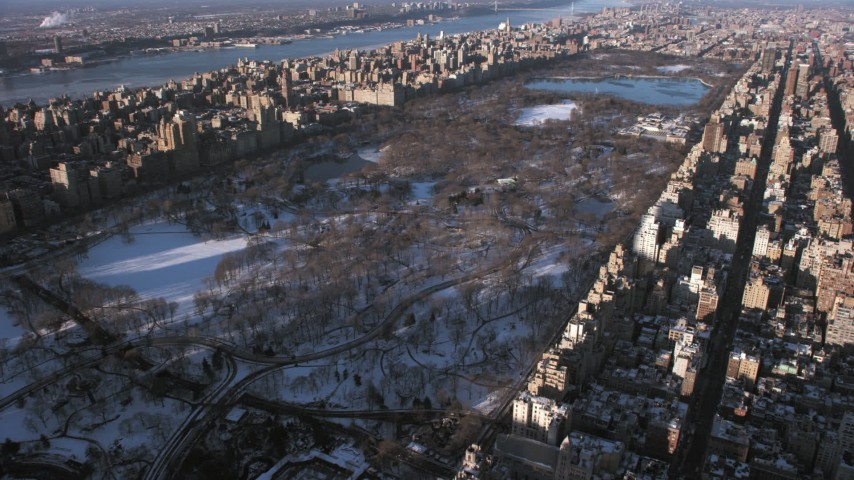 5K stock footage aerial video of passing Central Park in snow with bare trees, New York City Aerial Stock Footage | AX66_0189