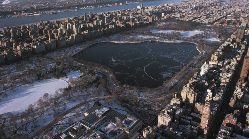 5K stock footage aerial video of Jacqueline Kennedy Onassis Reservoir in Central Park in snow, New York City Aerial Stock Footage | AX66_0191
