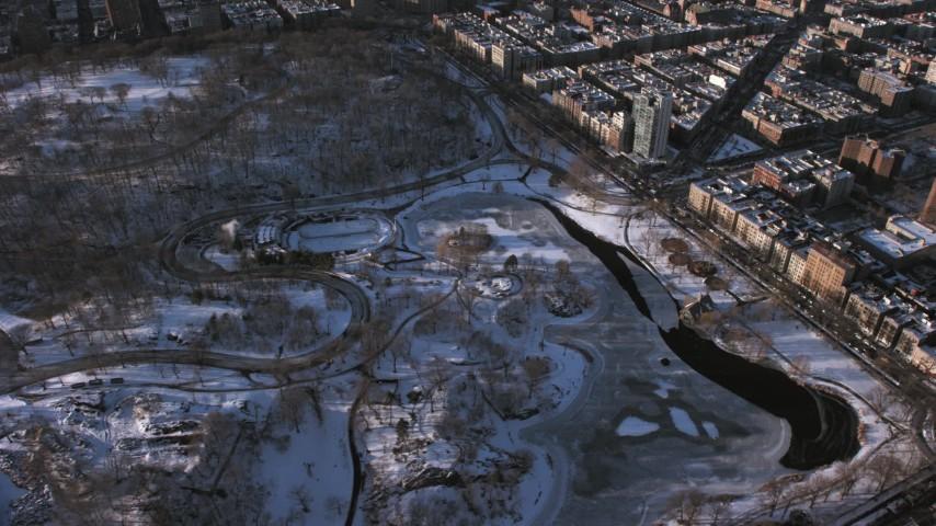 5K stock footage aerial video orbit Central Park skating rink in snow, Manhattan, New York City Aerial Stock Footage | AX66_0195